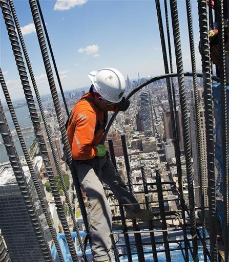 In this Wednesday, June 22, 2016 photo, a worker helps set another load of concrete into the walls of 3 World Trade Center in New York. The World Trade Center's latest new skyscraper has reached its full height of 80 stories. (AP Photo/Mark Lennihan)