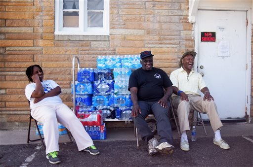 Stephanie Smith, left, Jimmie Thompson, center, and Otis Ross, right, share a laugh in-between residents coming to get water at Prince of Peace Baptist Church Wednesday, June 22, 2016 in northwest Flint. Every Monday, Wednesday and Friday the church gives