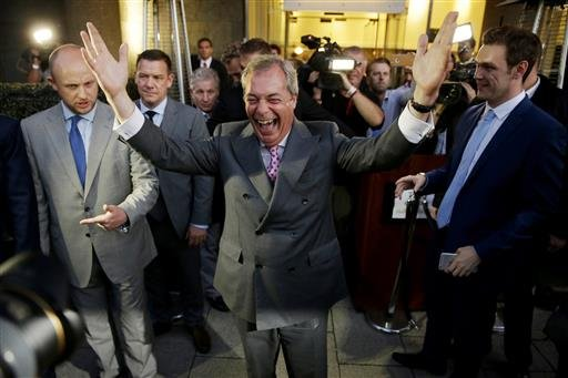 "Nigel Farage, the leader of the UK Independence Party, celebrates and poses for photographers as he leaves a ""Leave.EU"" organization party for the British European Union membership referendum in London, Friday, June 24, 2016."