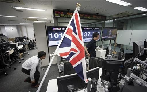Money traders walk past a flag of the United Kingdom at a foreign exchange brokerage at a securities firm in Tokyo, Friday, June 24, 2016.