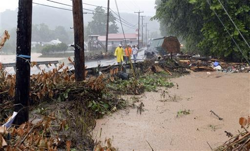In this photo made from video, debris from the Jordan Creek near Clendenin, W.Va., piles up against a culvert along U.S. 119 on Thursday night June 23, 2016, just before the creek's entry into the Elk River.