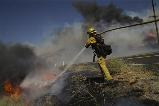 A firefighter puts out a wildfire burning along Highway 178 near Lake Isabella, Calif., Friday, June 24, 2016.