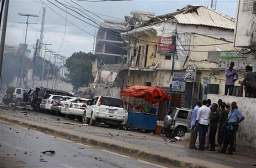 Security forces examine the scene after a bomb attack on Nasahablod Hotel in Mogadishu, Somalia, Saturday, June 25, 2016.