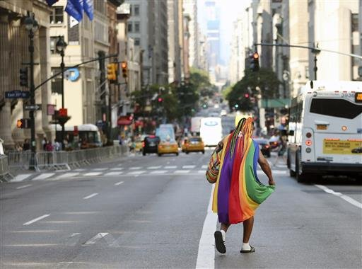 A person wearing a rainbow drape runs on Fifth Avenue before the New York City Pride Parade on Sunday, June 26, 2016, in New York City. A year after New York City's storied gay pride parade celebrated a high point with the legalization of gay marriage nat