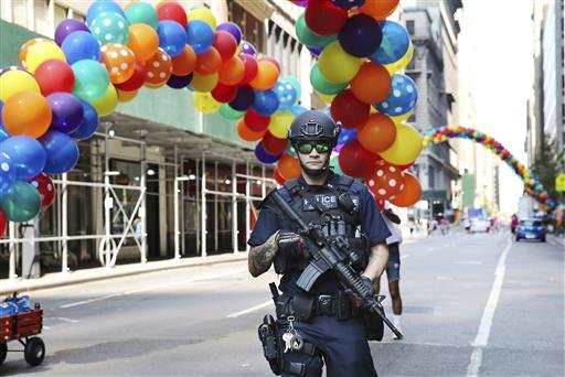 A heavily armed police officer stands in the street near the parade route of the New York City Pride Parade Sunday, June 26, 2016, in New York City. A year after New York City's storied gay pride parade celebrated a high point with the legalization of gay