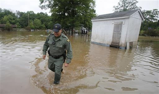 West Virginia State Trooper C.S. Hartman, walks from a shed that he checked out as he and other crews search homes in Rainelle, W. Va., Saturday, June 25, 2016. Heavy rains that pummeled West Virginia left multiple people dead, and authorities said Saturd