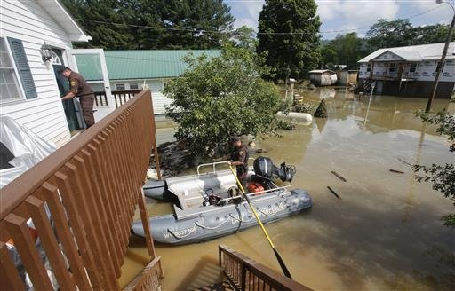 West Virginia Natural Resources police officer Chris Lester, left, walks into the top floor of a flooded home as he and Lt. Dennis Feazell search homes in Rainelle, W. Va., Saturday, June 25, 2016. About 32,000 West Virginia homes and businesses remain wi