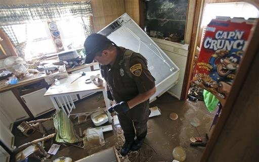 West Virginia Natural Resources police officer Chris Lester searches a flooded home in Rainelle, W. Va., Saturday, June 25, 2016. About 32,000 West Virginia homes and businesses remain without power Saturday after severe flooding hit the state. The West V