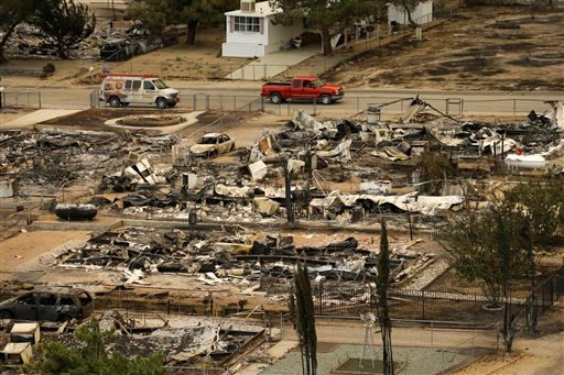 A pickup truck passes by the remains of mobile homes devastated by a wildfire, Saturday, June 25, 2016, in South Lake, Calif. (AP Photo/Jae C. Hong)