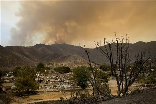 A scorched tree and devastated mobile homes are backdropped by a wildfire continuing to burn, Saturday, June 25, 2016, in South Lake, Calif. (AP Photo/Jae C. Hong)