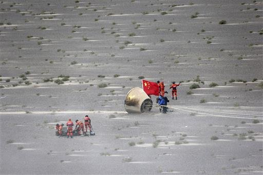 In this photo released by the Xinhua News Agency, workers retrieve a reentry module that was aboard the carrier rocket Long March-7 after it touches down successfully in Badain Jaran Desert in northern China's Inner Mongolia Autonomous Region, June 26, 20