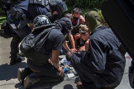 A victim is attended after he was stabbed during a rally at the State Capitol in Sacramento, Calif., on Sunday, June 26, 2016. Sacramento Fire Department spokesman Chris Harvey says a rally by KKK and other right-wing extremists groups turned violent Sund
