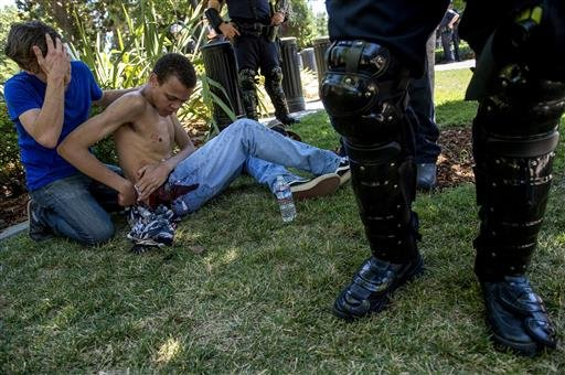 Sean Moore, 23, of Sacramento waits for medics with a friends after being stabbed by protesters at the State Capitol in Sacramento, Calif., on Sunday, June 26, 2016. Sacramento Fire Department spokesman Chris Harvey says a rally by KKK and other right-win