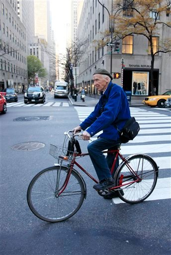In this Nov. 23, 2010 file photo, New York Times photographer Bill Cunningham bicycles to work in New York. Cunningham, a longtime fashion photographer for The New York Times known for taking pictures of everyday people on the streets in New York died on
