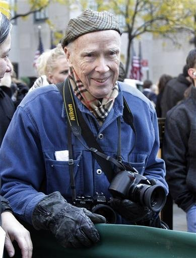 In this Nov. 11, 2011 file photo, New York Times photographer Bill Cunningham waits for the arrival of the annual Rockefeller Center Christmas tree, in New York. Cunningham, a longtime fashion photographer for The New York Times known for taking pictures