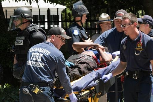 Paramedics rush a stabbing victim away on a gurney Sunday, June 26, 2016, after members of right-wing extremists groups holding a rally outside the California state Capitol building in Sacramento clashed with counter-protesters, authorities said. Sacramen