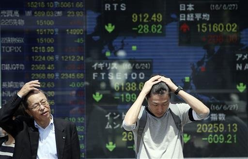 People stand in front of an electronic stock board of a securities firm in Tokyo, Monday, June 27, 2016. (AP Photo/Koji Sasahara)