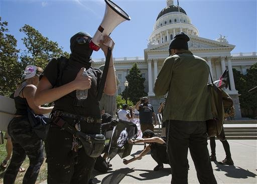 Members of ANTIFA Sacramento (Anti-Fascism Action) try to light a flag on fire as they stage a counter-protest against the Traditionalist Worker Party & Golden State Skinheads at Capitol in Sacramento 6/26/16.(Paul Kitagaki Jr./The Sacramento Bee via AP)