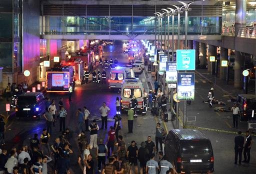 Medics and security members work at the entrance of the Ataturk Airport after explosions in Istanbul, Tuesday, June 28, 2016. Two explosions have rocked Istanbul's Ataturk airport, killing several people and wounding others, Turkey's justice minister and
