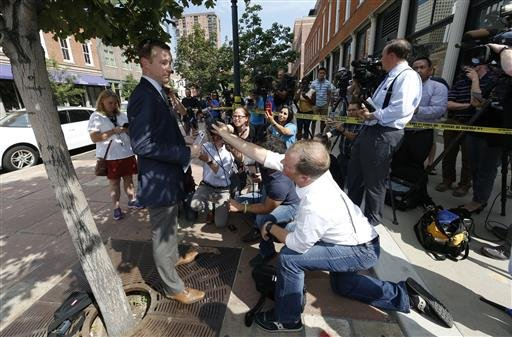 Doug Schepman, left, spokesperson for the Denver Police Department, responds to questions from reporters during a news conference near the scene of a shooting in a lower downtown business Tuesday, June 28, 2016, in Denver. Officers responded to the busine