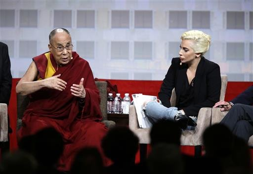Lady Gaga listens as the Dalai Lama speaks during a question and answer session at the the U.S. Conference of Mayors in Indianapolis, Sunday, June 26, 2016.