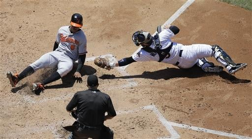 Baltimore Orioles' Jonathan Schoop, left, scores from third base off a throwing error as San Diego Padres catcher Derek Norris, is unable to make the tag during the fifth inning of a baseball game Wednesday, June 29, 2016, in San Diego.