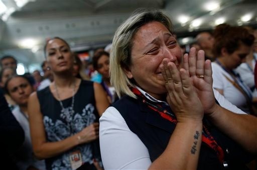 A woman reacts as Family members, colleagues and friends of the victims of Tuesday blasts gather for a memorial ceremony at the Ataturk Airport in Istanbul, Thursday, June 30, 2016.