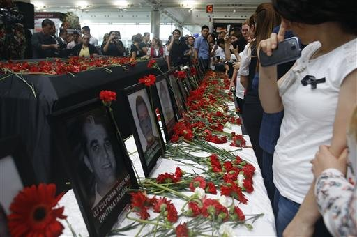 Photographs of victims were displayed among carnations as family members, colleagues and friends gather for a memorial ceremony at the Ataturk Airport in Istanbul, Thursday, June 30, 2016.