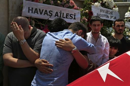 Relatives gather around the Turkish flag-draped coffin of Habibullah Sefer, one of the victims killed Tuesday at the blasts in Istanbul's Ataturk airport, during the funeral in Istanbul, Thursday, June 30, 2016.