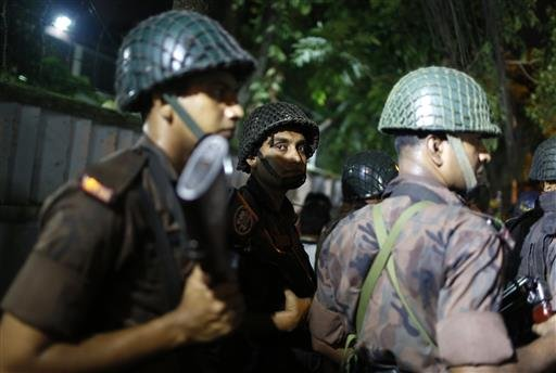 Bangladeshi security personnel stand guard near a restaurant that has reportedly been attacked by unidentified gunmen in Dhaka, Bangladesh, Friday, July 1, 2016.