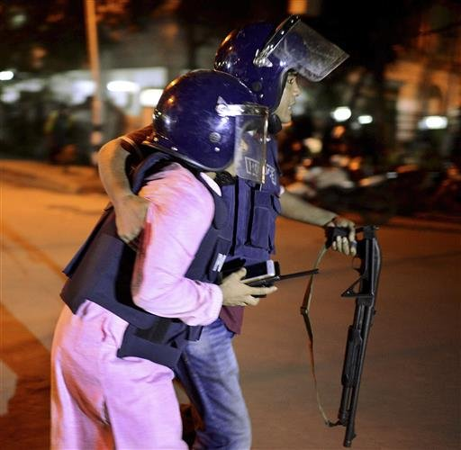 An unidentified security personnel is taken for medical attention after a group of gunmen attacked a restaurant popular with foreigners in a diplomatic zone of the Bangladeshi capital Dhaka, Bangladesh, Friday, July 1, 2016.