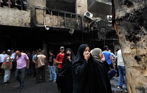 Iraqi women wait to hear about family members who went missing after a car bomb hit Karada, a busy shopping district in the center of Baghdad, Iraq, Sunday, July 3, 2016. Dozens of people have been killed and more than 100 wounded in two separate bomb att