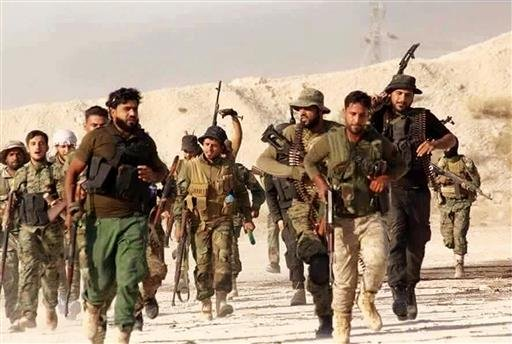 This file photo released Tuesday June 28, 2016 by the New Syrian Army, an anti-government rebel group, which has been authenticated based on its contents and other AP reporting, shows U.S.-backed Syrian rebels of the New Syrian Army running in an unknown