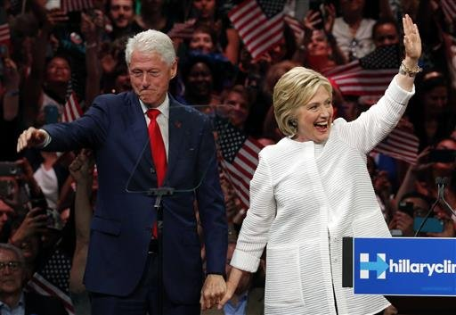 In this June 7, 2016, file photo, former President Bill Clinton, left, stands on stage with his wife, Democratic presidential candidate Hillary Clinton, after she spoke during a presidential primary election night rally in New York. His popularity among