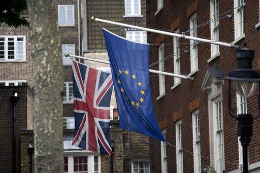 In this Wednesday, June 22, 2016, file photo, a European, right, and Union flag are displayed outside Europe House, the European Parliament's British offices, in London. One week after Britain's vote to quit the EU sent markets into a tailspin, investors