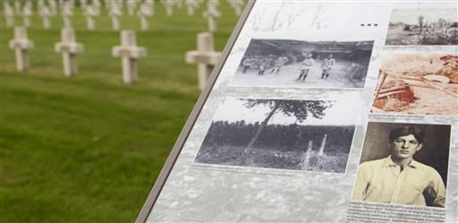 In this photo taken on Wednesday, June 8, 2016, an information board with a photograph of Alan Seeger guides visitors through the French National Necropolis of Lihons, in Lihons, France. American poet Alan Seeger died a century ago on July 4th during the