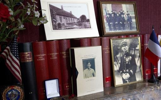 In this photo taken on Wednesday, June 8, 2016, a photograph of American poet Alan Seeger and other mementos line a mantle piece in the Mayors office of Belloy-en-Santerre, France. American poet Alan Seeger died a century ago on July 4th during the 1916 B