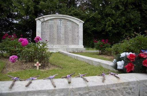 In this photo taken on Wednesday, June 8, 2016, Wooden crosses with ribbons in the French national colors line a border around Ossuary No.1 at the French National Necropolis of Lihons, in Lihons, France. American poet Alan Seeger died a century ago on Jul