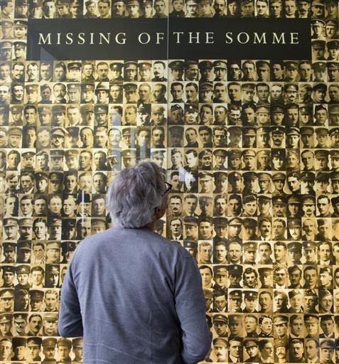 In this photo taken on Wednesday, June 8, 2016, a visitor looks at photos of soldiers who died or who were declared missing during the Battle of the Somme, at the Thiepval Memorial in Authuille, France. American poet Alan Seeger died a century ago on July