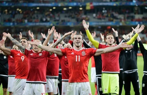 Wales' Gareth Bale, center, celebrates with his teammates after their 3-1 win at the end of the Euro 2016 quarterfinal soccer match between Wales and Belgium, at the Pierre Mauroy stadium in Villeneuve d'Ascq, near Lille, France, Friday, July 1, 2016. (AP