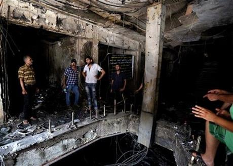 Iraqi men look for victims who went missing after a car bomb hit Karada, a busy shopping district in the center of Baghdad, Iraq, Monday, July 4, 2016. More than 100 people died Sunday in a car bombing that Islamic State said it carried out, an official o