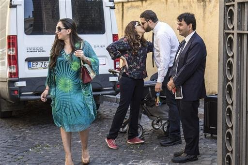 Public relations expert Francesca Chaouqui, second from left, kisses her husband Corrado Lanino, as they arrive at the Vatican for her trial, Tuesday, July 5, 2016.