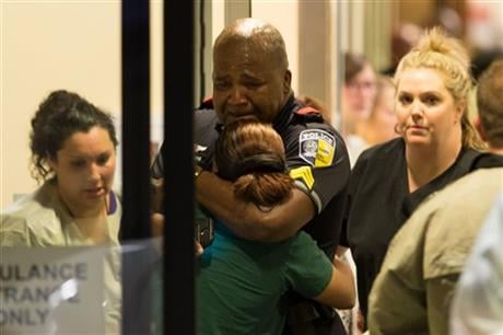 A Dallas Area Rapid Transit police officer receives comfort at the Baylor University Hospital emergency room entrance Thursday, July 7, 2016, in Dallas. AP