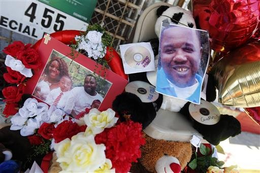 Photos of Alton Sterling are interspersed with flowers and mementos at a makeshift memorial in front of the Triple S Food Mart in Baton Rouge, La., Thursday, July 7, 2016.