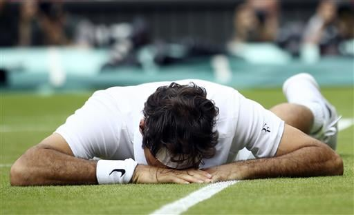 Roger Federer of Switzerland falls over during his men's semifinal singles match against Milos Raonic of Canada.