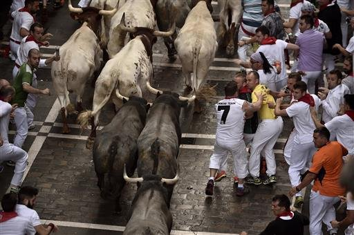 Revelers run with Jose Escolar Gil's fighting bulls as they head towards Estafeta street during the third running of the bulls at the San Fermin Festival, in Pamplona, northern Spain, Saturday, July 9, 2016.