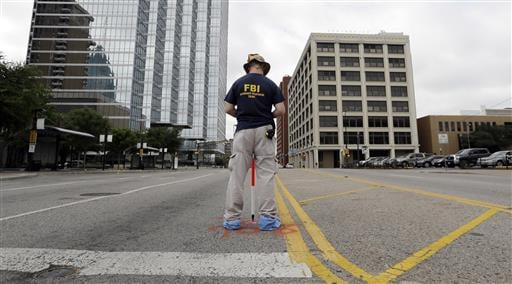 Investigators work in the area of downtown Dallas that remains an active crime scene, Saturday, July 9, 2016.