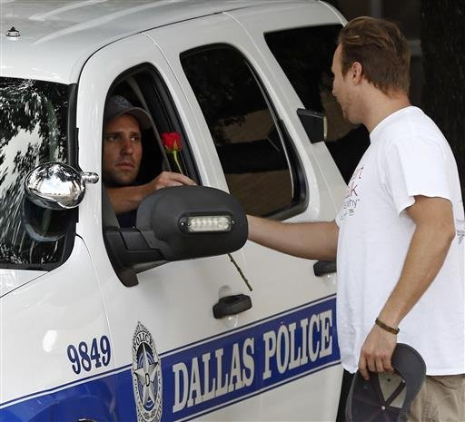 John Fife hands a police officer guarding Jack Evans Police Headquarters a rose in Dallas on Friday July 8, 2016.