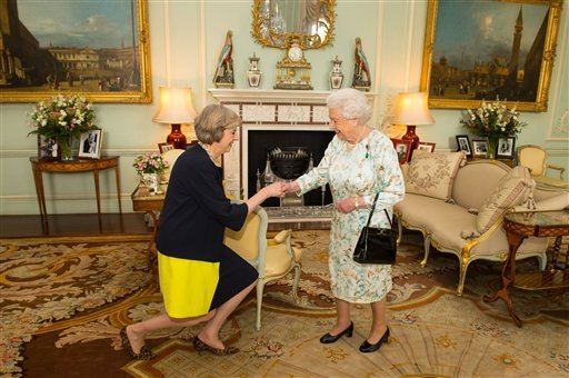 Queen Elizabeth II welcomes Theresa May, left, at the start of an audience in Buckingham Palace, London.