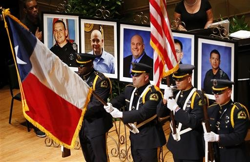 The Dallas Police color guard presents the colors before the photos of five fallen officers being remembered during an interfaith memorial service at the Morton H. Meyerson Symphony Center in Dallas, Tuesday, July 12, 2016.